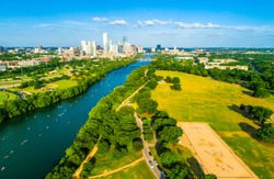 paddle Boarders and kayakers line up along Lady Bird Lake in Austin Texas skyline cityscape aerial drone view above green landscape Barton creek flowing into town lake