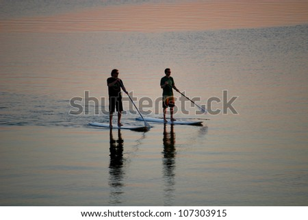 paddle boarders at dusk