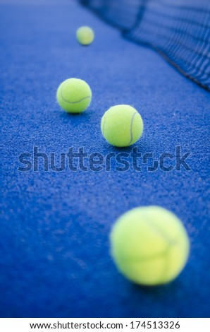 paddle tennis or tennis balls on artificial turf ready for tournament with hard dramatic shadows.