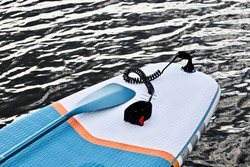 Paddleboard and surf board with paddle on wavy water surface background close up. Surfing and SUP boarding equipment in bright sunlight close-up. Outdoor water sports. Surfing lifestyle backgrounds.