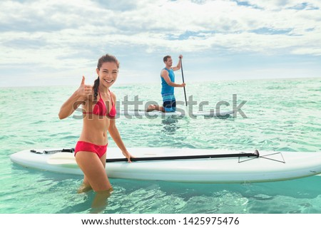 Paddleboard beach people on stand-up paddle boards surfing in ocean on Hawaii beach. Mixed race couple woman and Caucasian man enjoying watersport. #1425975476