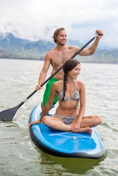 Paddleboard couple having fun paddleboarding together on Hawaii beach vacation summer holidays. Woman sitting on board while man paddles.