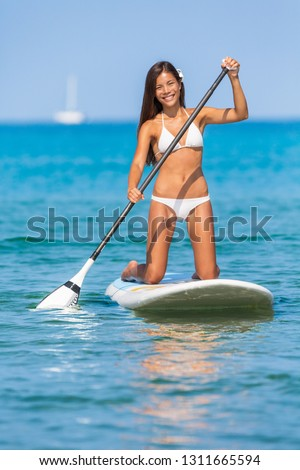 Paddleboard SUP Asian girl having fun paddle board in Hawaii. Fitness recreational leisure activity. Beach rental equipment on travel vacation. Bikini Chinese multiracial woman.