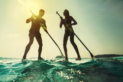 Paddleboarding at sunset. Young couple in the sea with paddle and board.