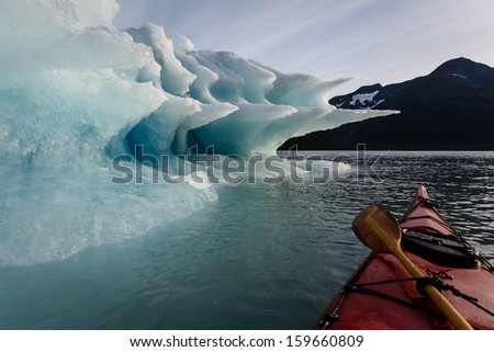 Paddler lashes paddle to kayak to pause journey to enjoy the splendor of the shapes of the  melting Iceberg in summertime Alaska's Kenai Fiords National Park
