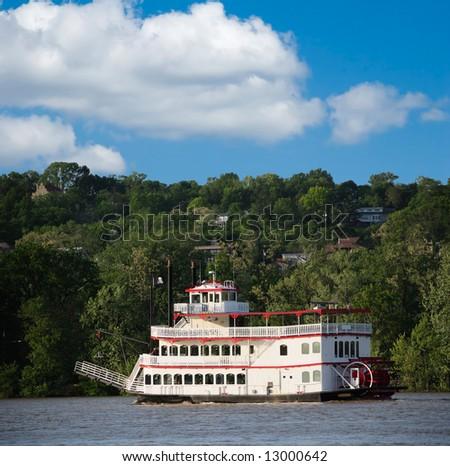 Paddlewheel riverboat traveling down the Ohio river toward Cincinnati in summer.