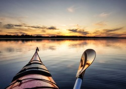 Paddling on red kayak towards sunset, absolutely calm water in Stocksjo Lake, close to Umea City, Vasterbotten County, Northern Sweden. No people and absolutely quiet on this summer evening