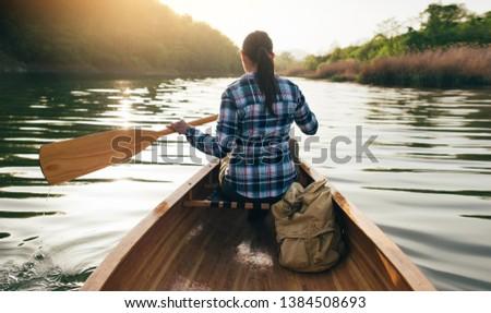 Paddling the wooden canoe. Rear view of travel girl canoeing on the sunset lake. Kayaking, canoeing, outdoors