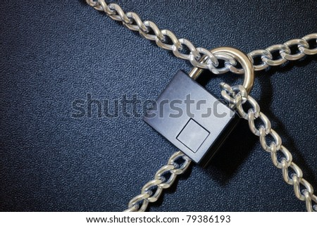 Padlock and chain on dark background - stock photo