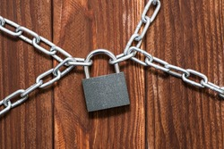Padlock and chain on wooden background. Metal chain and locked padlock on wooden background. Safety concept.