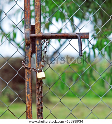 Padlock and old chain on metal fence