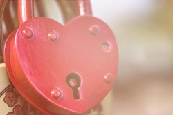 Padlock in the form of a big red heart with a hole in the soft sunlight. The concept of love, relationships, marriage, wedding. selective focus