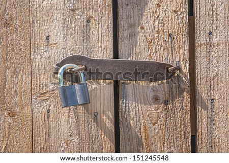 Padlock on a old brown wooden door