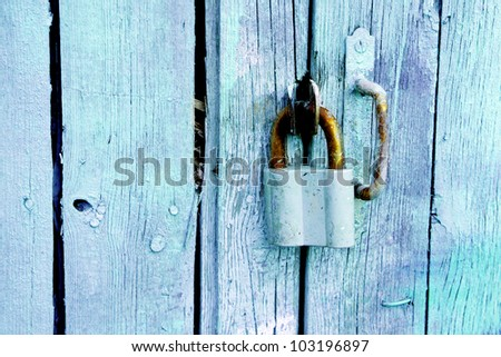 padlock on an old blue wooden fence