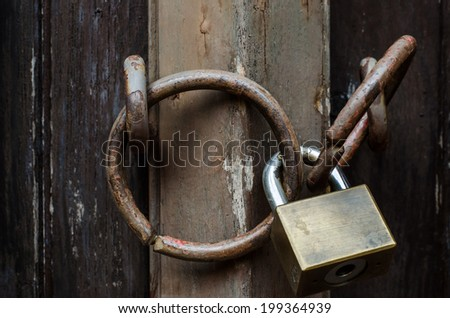 Padlock on ancient style wooden door, close up.