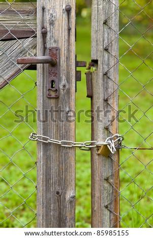 Padlock on fence door - stock photo