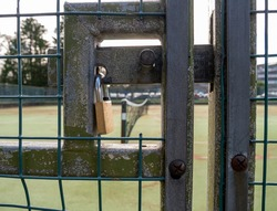 Padlock on gate to tennis courts. The net is visible in the background