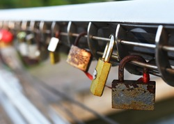 Padlock on Lovers Lock Bridge. Husband and wife during the wedding hung a padlock on the fence on metal grate. Love locks concept. Many a padlock are locked with a key for the happiness of people