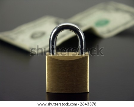 Padlock with an out of focus dollar bill in the background.