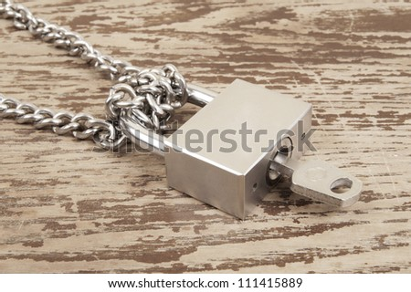 Padlock with key and chain on wooden table