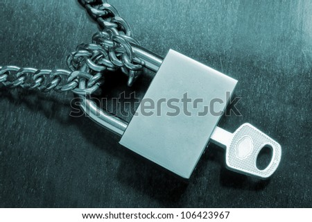 Padlock with key and chainon wooden table
