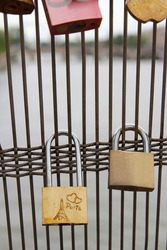 Padlock with the Eiffel Tower carving hanging on the fence of Passerelle Leopold Sedar Senghor footbridge in Paris