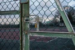 Padlocked gates of tennis courts at local park during lockdown