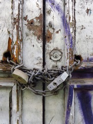 Padlocks and rusty iron chain on broken white old wooden door with violet graffiti. Locks on a chain hangs on a door. Old metal padlocks on a uncorked wooden door.