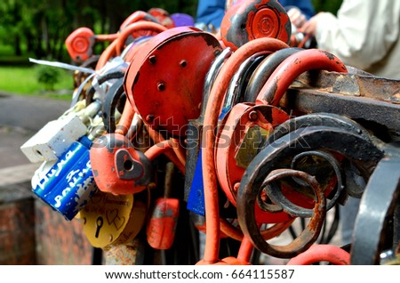 Padlocks are hanging on a fence that hanged lovers #664115587