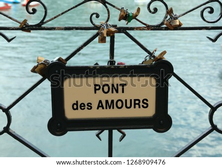 padlocks hanging by the lovers on the bridge with the text PONT de AMOURS which means Bridge of the Lovers in French language