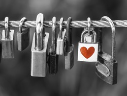 Padlocks with heart shape on rope bridge over black and white background, Valentines day concept.
