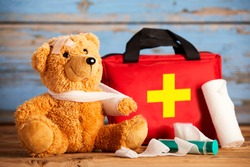 Paediatric healthcare concept with a little teddy bear with its arm in a sling alongside a first aid kit and bandages on rustic wood