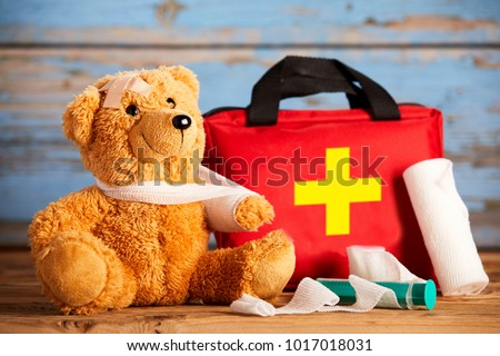 Paediatric healthcare concept with a little teddy bear with its arm in a sling alongside a first aid kit and bandages on rustic wood #1017018031