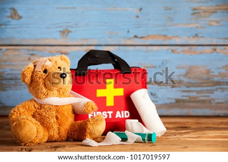 Paediatric healthcare concept with a little teddy bear with its arm in a sling alongside a first aid kit and bandages on rustic wood #1017019597
