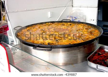 Paella cooking in large pan at market