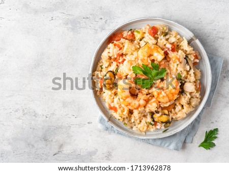 Paella traditional spanish dish. Seafood and chicken paella.Rice, mussles, shrimps,chicken, tomatoes and chopped parsley stewed in wine.Served in grey ceramic plates on concrete background. Copy space