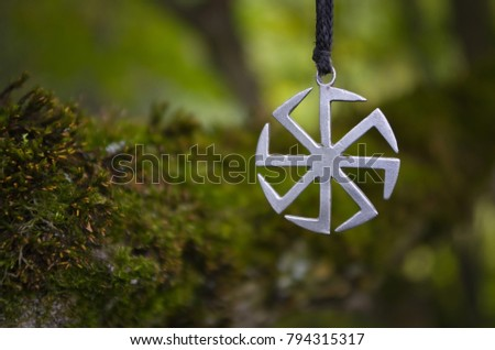 Pagan symbol Kolovrat on the background of moss. #794315317