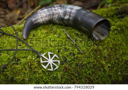 Pagan symbolism of cow horn and an ancient symbol of Kolovrat on the forest moss. #794318029