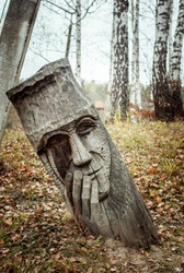 Pagan wooden idol made of wood carved face in the ground