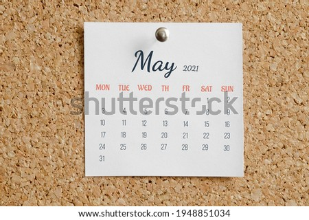 Page from the calendar for the full month: May 2021. White calendar sheet is attached to brown cork board. The concept of calendar date.