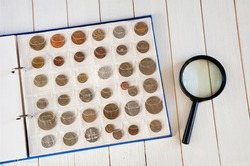 Page of numismatics album with different coins on a white wooden table