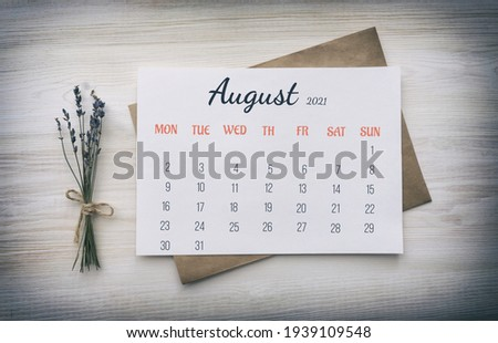 Page of the month: August 2021. Paper calendar on white paper, on top of kraft paper envelope, next to bouquet of dried lavender on wooden white background. The concept of calendar date, full month
