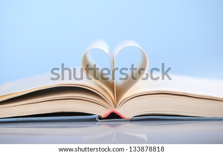 Pages of a book curved into a heart shape on blue background