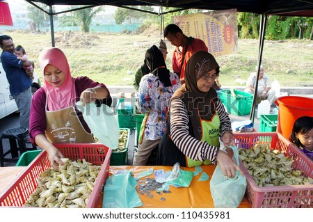 PAHANG, M'SIA-AUG 18: Unidentified traditional food seller attends to a customer at Pasar Ramadan Kuantan on August 18, 2012 in Pahang, Malaysia. Muslims around the world celebrate Aidilfitri tomorrow