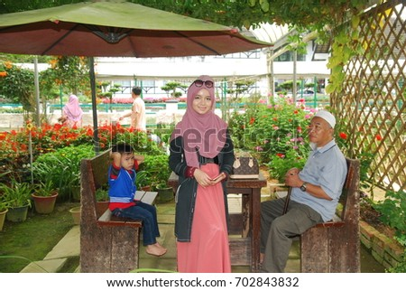 PAHANG, MALAYSIA - August 10, 2017: undentified family poses over flower farm background in Cameron Highland, Malaysia.   #702843832