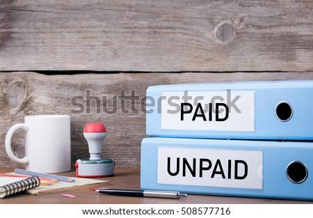 Paid and Unpaid. Two binders on desk in the office. Business background