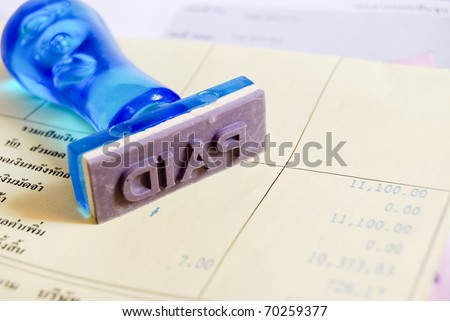 paid letter on rubber stamp with business cash receipt paper background