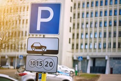 Paid parking zone for cars. Park sign at outdoor crowded car parking lot. Parking problems in the city.