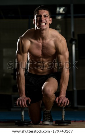 Pain and Gain - Young Muscular Men Kneeling On The Floor With A Pair Of Dumbbells