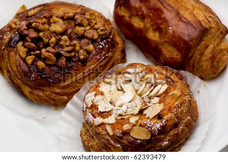 Pain au chocolat, cinnamon walnut, and apricot almond pastries on white plate.